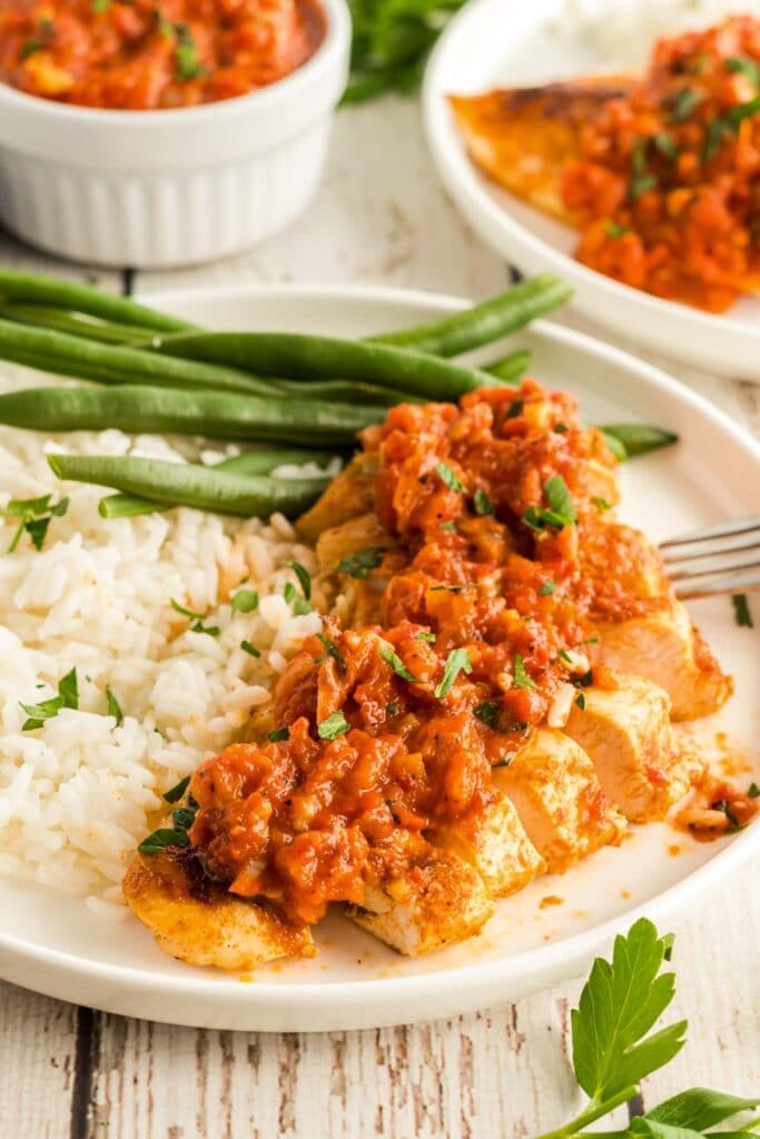 chicken romesco on a plate with green beans