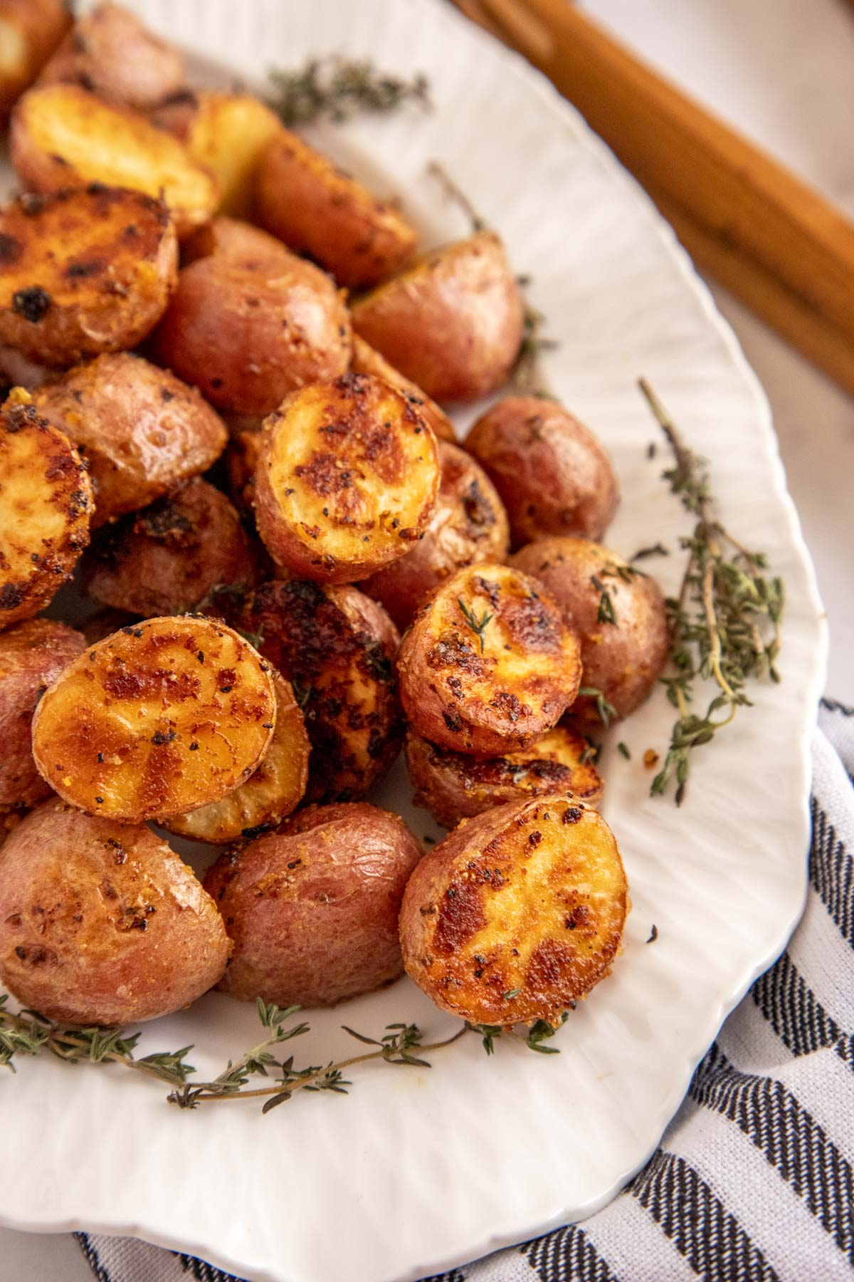 roasted baby potatoes on a white platter with a striped napkin
