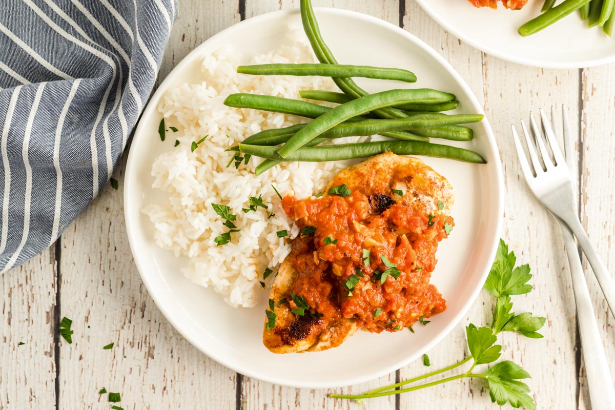 white plate with chicken, rice, green beans