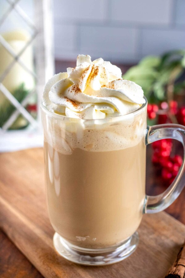 eggnog latte in a glass mug with whipped cream