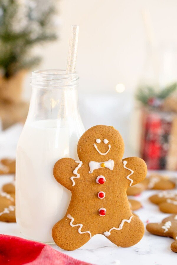 gingerbread man leaning on a glass of milk