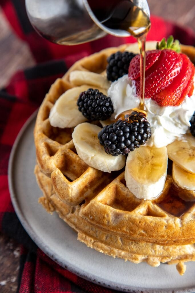 syrup being poured over fruit topped waffles
