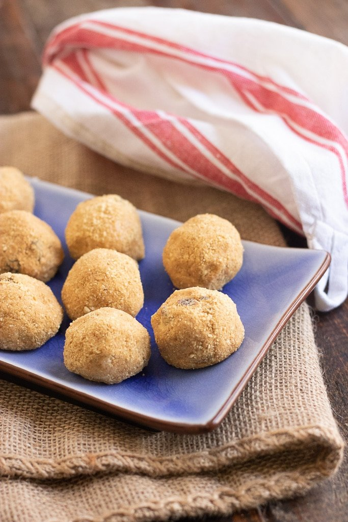 Peanut butter protein balls on blue serving dish on tweed mat.