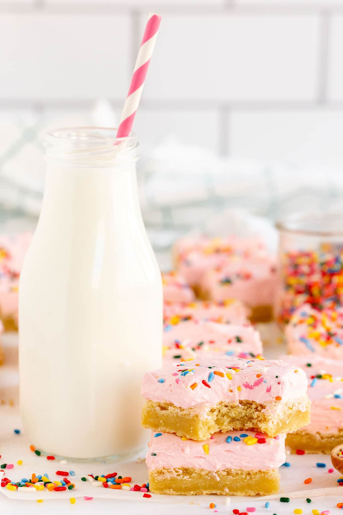 sugar cookie bars with pink frosting and milk