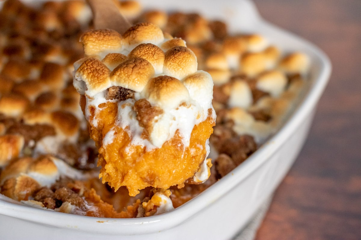 sweet potato casserole in a white dish with a spoon