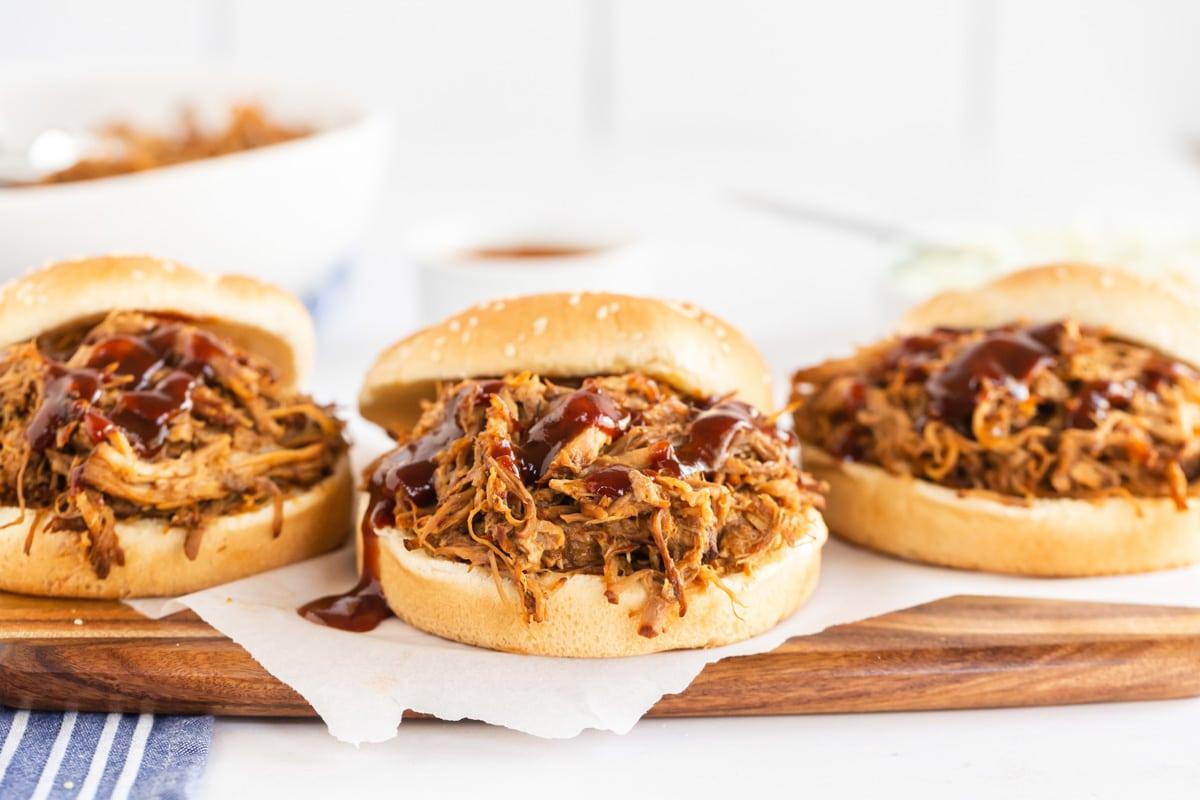 3 pulled pork sandwiches on sesame buns