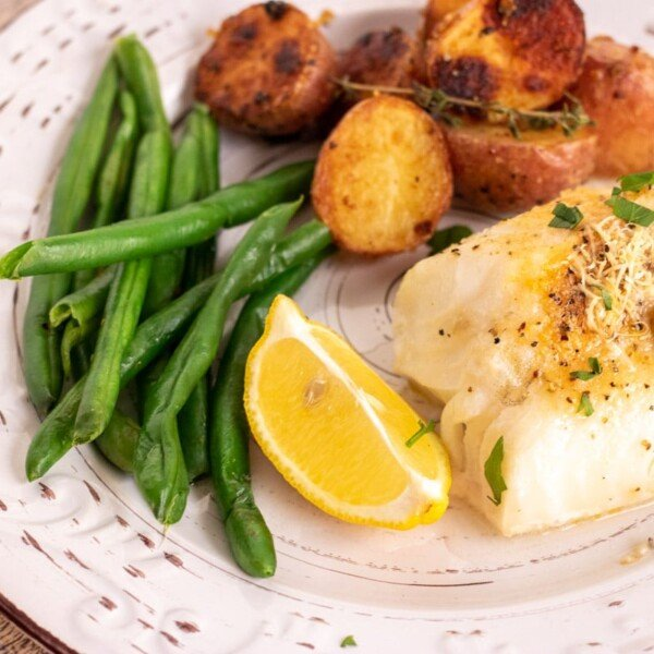 baked fish with lemon on a white plate with vegetables