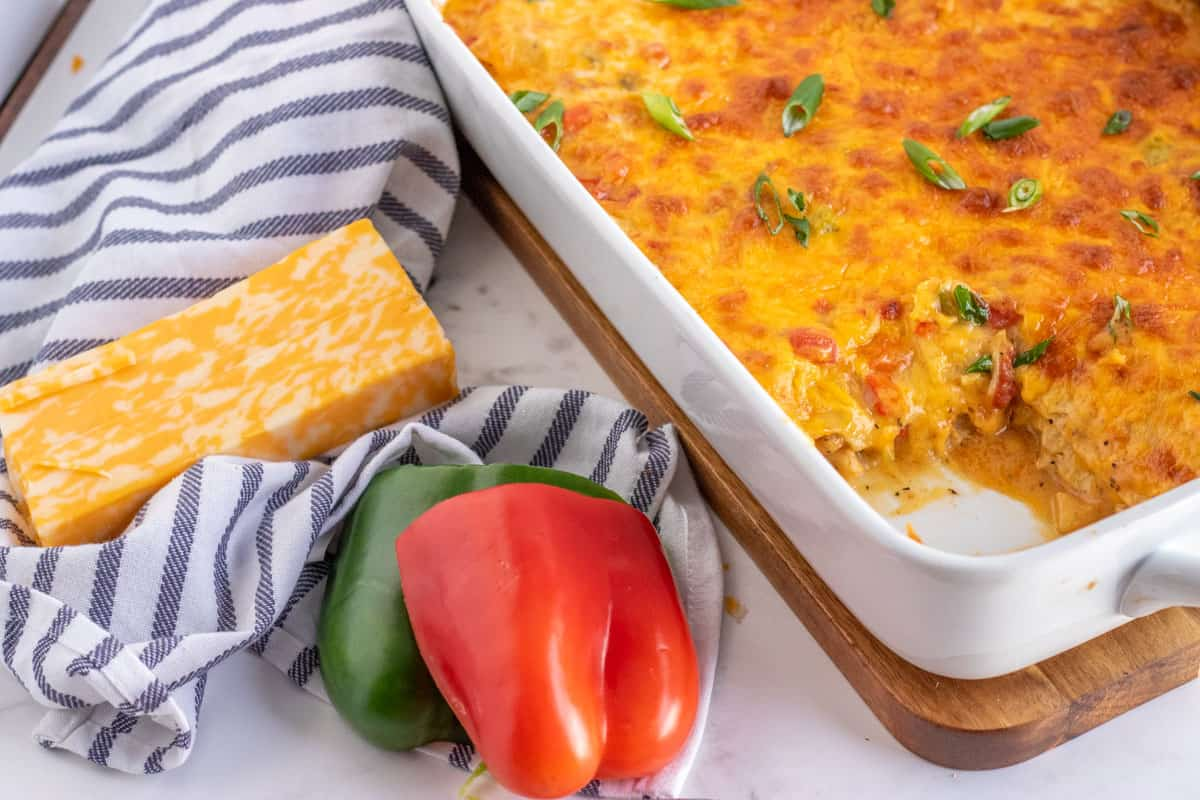 casserole in a white dish with green and red bell peppers and cheese