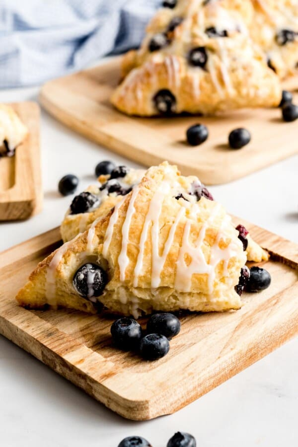Blueberry scones with vanilla glaze on a wooden board