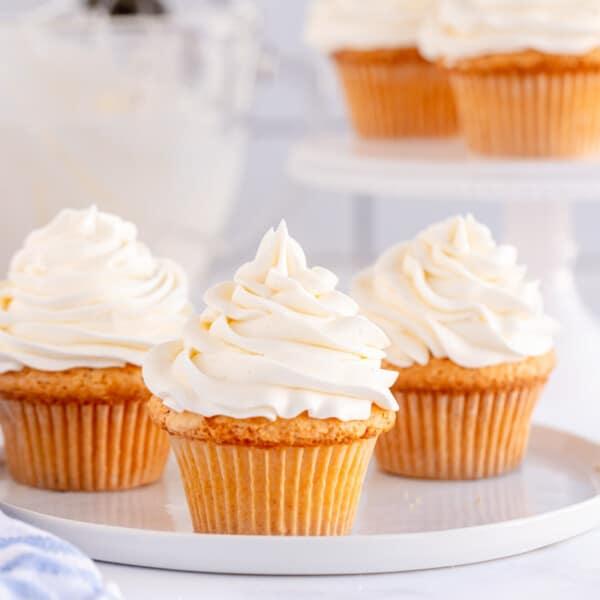 3 vanilla cupcakes with vanilla frosting