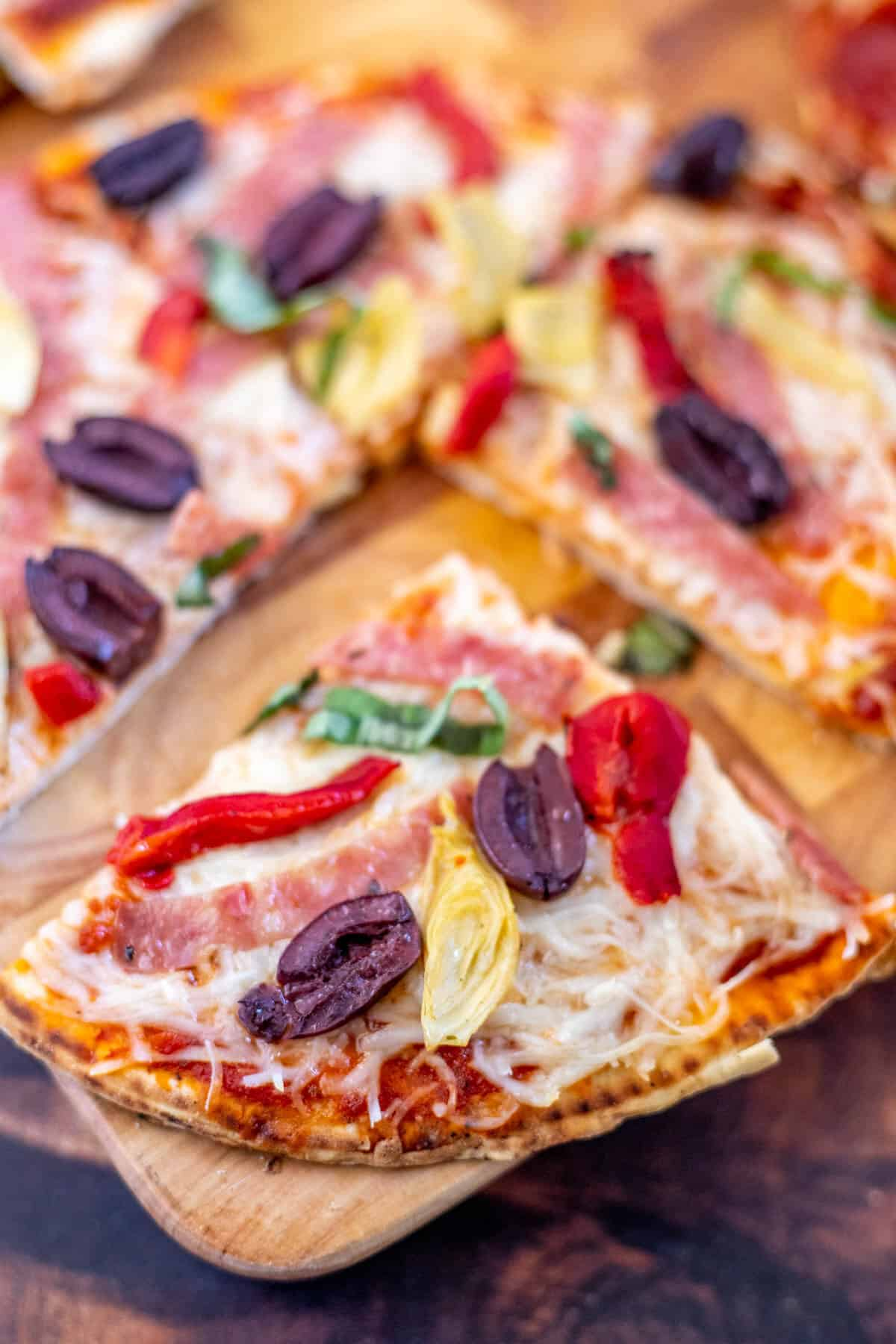 slices of flatbread pizza on a wooden board