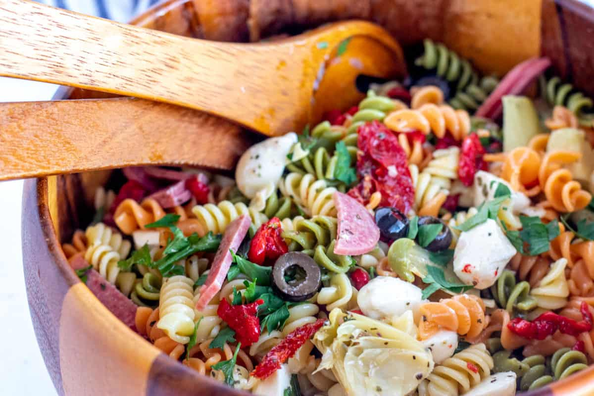 Antipasto salad in a wooden bowl with spoons