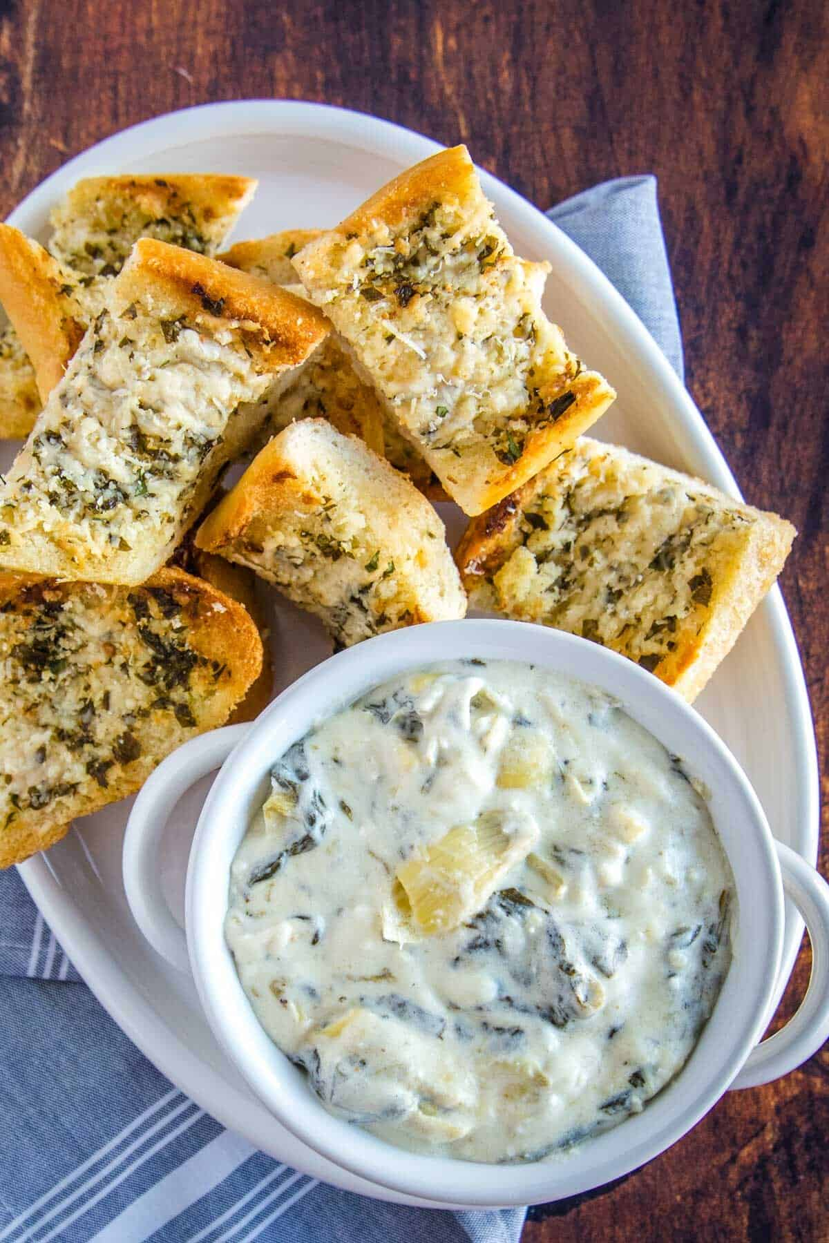 overhead of spinach artichoke dip, on a white platter