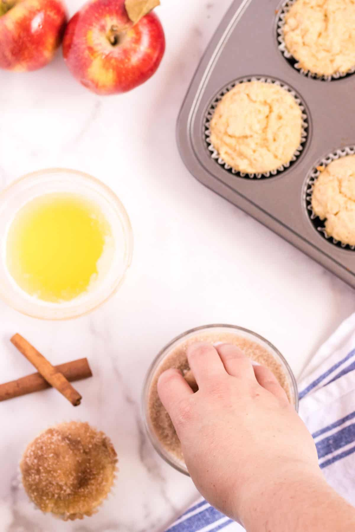 hand dipping muffins into cinnamon sugar