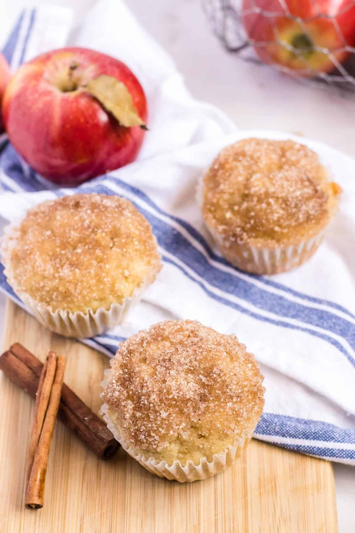 applesauce muffins on a wooden board with apples and cinnamon sticks
