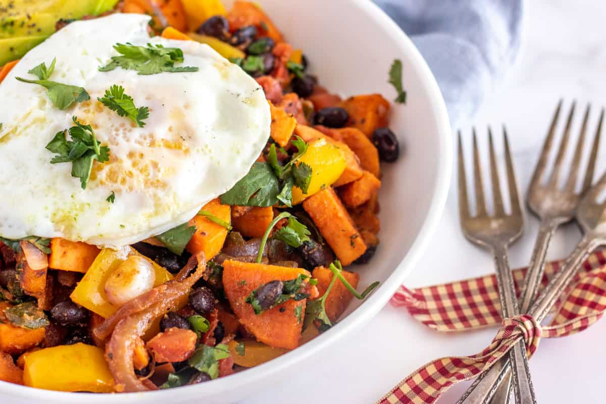 sweet potato hash with an egg, and avocado slices in a white bowl
